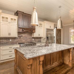 Amerikansk inredning av ett mellanstort linjärt kök och matrum, med en undermonterad diskho, luckor med infälld panel, granitbänkskiva, rött stänkskydd, stänkskydd i tegel, rostfria vitvaror, mörkt trägolv, en köksö och beige skåp
