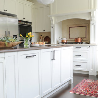 Inspiration for a mid-sized transitional u-shaped separate kitchen in Vancouver with an undermount sink, recessed-panel cabinets, white cabinets, wood benchtops, beige splashback, terra-cotta splashback, stainless steel appliances, dark hardwood floors and with island.