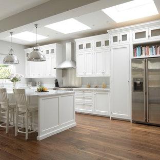 ロンドンの広いトラディショナルスタイルのおしゃれなキッチン (シェーカースタイル扉のキャビネット、白いキャビネット、シルバーの調理設備、濃色無垢フローリング) の写真