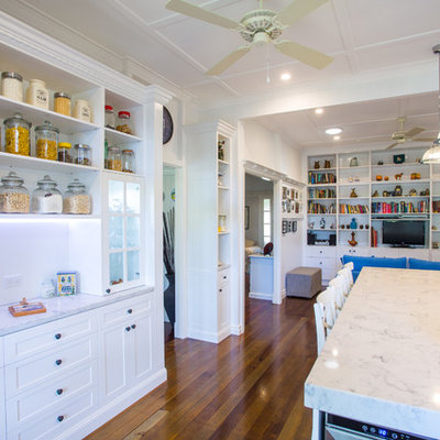 Eat-in kitchen - large traditional galley dark wood floor eat-in kitchen idea in Brisbane with shaker cabinets, white cabinets, white backsplash, colored appliances, an island, a farmhouse sink, solid surface countertops and subway tile backsplash