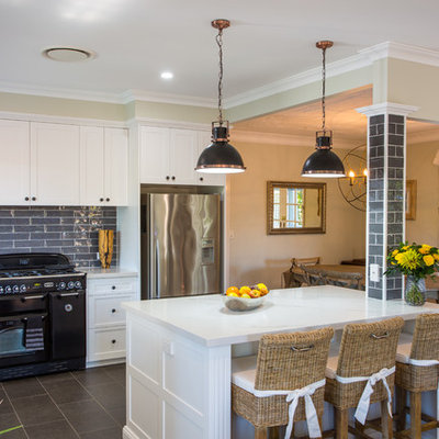 Example of a large classic l-shaped ceramic tile and gray floor open concept kitchen design in Brisbane with an undermount sink, shaker cabinets, white cabinets, quartz countertops, gray backsplash, black appliances and an island