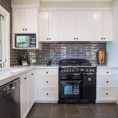 Open concept kitchen - large traditional l-shaped ceramic tile and gray floor open concept kitchen idea in Brisbane with an undermount sink, shaker cabinets, white cabinets, quartz countertops, gray backsplash, subway tile backsplash, black appliances and an island