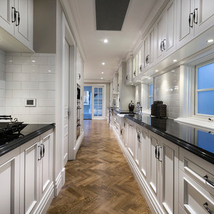 Inspiration for an expansive traditional galley kitchen in Perth with an undermount sink, recessed-panel cabinets, beige cabinets, granite benchtops, white splashback, ceramic splashback, stainless steel appliances, dark hardwood floors and with island.