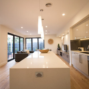 Mid-sized contemporary eat-in kitchen inspiration - Eat-in kitchen - mid-sized contemporary galley light wood floor eat-in kitchen idea in Melbourne with a drop-in sink, concrete countertops, gray backsplash, glass sheet backsplash, stainless steel appliances and an island