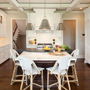 Photo of a large classic u-shaped kitchen/diner in Minneapolis with a belfast sink, recessed-panel cabinets, white cabinets, marble worktops, white splashback, metro tiled splashback, stainless steel appliances, dark hardwood flooring and an island.
