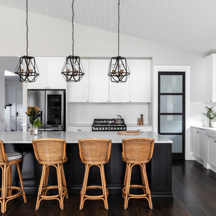 Inspiration for a transitional l-shaped kitchen in Brisbane with a farmhouse sink, shaker cabinets, white cabinets, white splashback, stainless steel appliances, dark hardwood floors, with island, brown floor and white benchtop.