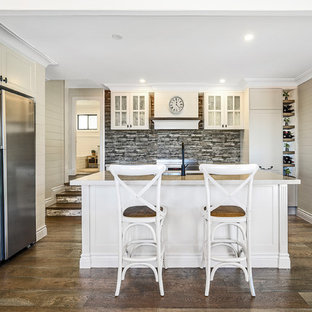 Design ideas for a beach style kitchen in Gold Coast - Tweed with glass-front cabinets, white cabinets, multi-coloured splashback, stainless steel appliances, dark hardwood floors and with island.