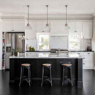 Ejemplo de cocina de galera, clásica renovada, abierta, con fregadero bajoencimera, armarios estilo shaker, puertas de armario blancas, salpicadero blanco, salpicadero de azulejos tipo metro, electrodomésticos de acero inoxidable, una isla y suelo negro