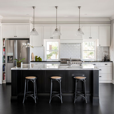 Inspiration for a transitional galley black floor open concept kitchen remodel in Brisbane with an undermount sink, shaker cabinets, white cabinets, white backsplash, subway tile backsplash, stainless steel appliances and an island