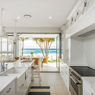 Design ideas for a large beach style galley eat-in kitchen in Gold Coast - Tweed with a farmhouse sink, shaker cabinets, white cabinets, marble benchtops, white splashback, marble splashback, stainless steel appliances, ceramic floors, with island, beige floor and white benchtop.