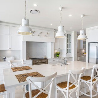 Inspiration for a large beach style galley eat-in kitchen in Gold Coast - Tweed with a farmhouse sink, shaker cabinets, white cabinets, marble benchtops, white splashback, marble splashback, stainless steel appliances, ceramic floors, with island, beige floor and white benchtop.