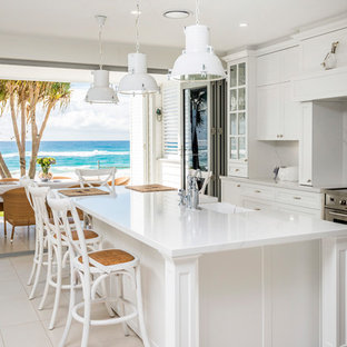 Large beach style galley eat-in kitchen in Gold Coast - Tweed with a farmhouse sink, white cabinets, marble benchtops, white splashback, marble splashback, stainless steel appliances, ceramic floors, with island, beige floor, white benchtop and recessed-panel cabinets.