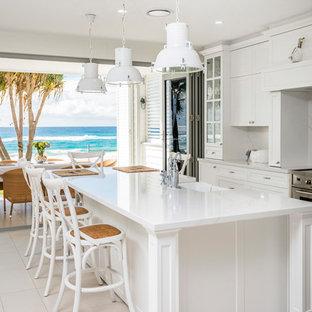 Zweizeilige, Große Maritime Wohnküche mit Landhausspüle, weißen Schränken, Marmor-Arbeitsplatte, Küchenrückwand in Weiß, Rückwand aus Marmor, Küchengeräten aus Edelstahl, Keramikboden, Kücheninsel, beigem Boden, weißer Arbeitsplatte und Schrankfronten mit vertiefter Füllung in Gold Coast - Tweed
