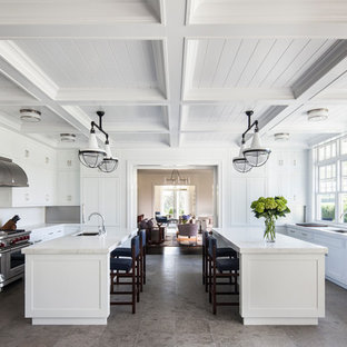 Design ideas for an expansive traditional galley separate kitchen in New York with an undermount sink, shaker cabinets, white cabinets, white splashback, stainless steel appliances, multiple islands, grey floor, marble benchtops, stone slab splashback and porcelain floors.