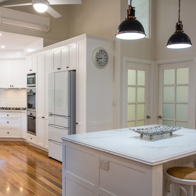 Open concept kitchen - large traditional u-shaped open concept kitchen idea in Brisbane with shaker cabinets, white cabinets, quartz countertops, white backsplash and an island