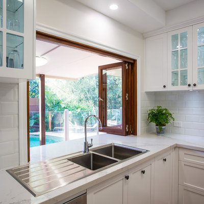 Inspiration for a large timeless u-shaped medium tone wood floor and brown floor open concept kitchen remodel in Brisbane with a double-bowl sink, shaker cabinets, white cabinets, quartz countertops, white backsplash, subway tile backsplash, black appliances and an island