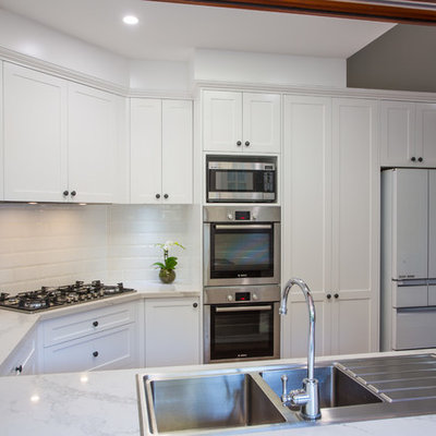 Example of a large classic u-shaped medium tone wood floor and brown floor open concept kitchen design in Brisbane with a double-bowl sink, shaker cabinets, white cabinets, quartz countertops, white backsplash, subway tile backsplash, stainless steel appliances and an island