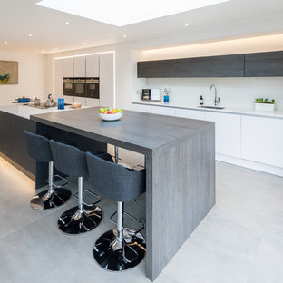 Design ideas for a large contemporary single-wall open plan kitchen in West Midlands with a single-bowl sink, quartz worktops, white splashback, glass sheet splashback, black appliances, porcelain flooring, an island, grey floors, flat-panel cabinets, white cabinets and white worktops.