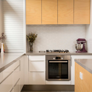 Example of a small minimalist l-shaped concrete floor eat-in kitchen design in Perth with light wood cabinets, quartz countertops, gray backsplash, ceramic backsplash, stainless steel appliances and an island
