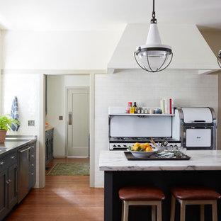 ロサンゼルスの地中海スタイルのおしゃれなキッチン (ダブルシンク、シェーカースタイル扉のキャビネット、グレーのキャビネット、ステンレスカウンター、白いキッチンパネル、サブウェイタイルのキッチンパネル、白い調理設備、無垢フローリング、茶色い床、グレーのキッチンカウンター) の写真