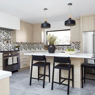 ロサンゼルスの広いコンテンポラリースタイルのおしゃれなキッチン (アンダーカウンターシンク、フラットパネル扉のキャビネット、淡色木目調キャビネット、人工大理石カウンター、マルチカラーのキッチンパネル、セメントタイルのキッチンパネル、シルバーの調理設備、グレーの床、白いキッチンカウンター) の写真