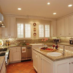 ロサンゼルスの地中海スタイルのおしゃれなアイランドキッチン (タイルカウンター、磁器タイルのキッチンパネル、シルバーの調理設備) の写真
