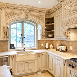 Design ideas for a mid-sized traditional u-shaped separate kitchen in New York with a farmhouse sink, raised-panel cabinets, beige cabinets, marble benchtops, beige splashback, ceramic splashback, stainless steel appliances, ceramic floors, with island, beige floor and beige benchtop.