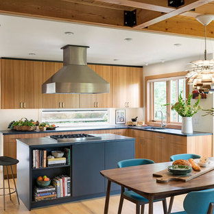 Midcentury modern eat-in kitchen inspiration - 1960s l-shaped light wood floor eat-in kitchen photo in Minneapolis with an undermount sink, flat-panel cabinets, light wood cabinets, window backsplash, an island and black countertops