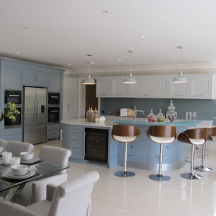 Photo of a large modern kitchen/diner in Surrey with recessed-panel cabinets, white cabinets, composite countertops, blue splashback, glass sheet splashback, stainless steel appliances and an island.