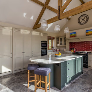 Large rural l-shaped kitchen in Hertfordshire with recessed-panel cabinets, red splashback, metro tiled splashback, an island, grey floors and grey worktops.