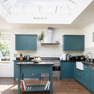 Inspiration for a classic l-shaped kitchen in Surrey with a belfast sink, shaker cabinets, grey splashback, metro tiled splashback, stainless steel appliances, an island, black worktops, blue cabinets, granite worktops and dark hardwood flooring.