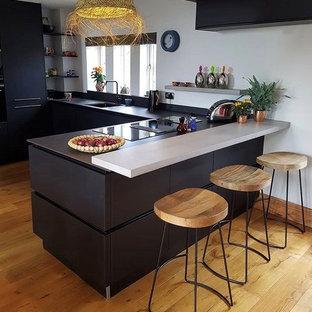 Design ideas for a medium sized eclectic u-shaped kitchen/diner with a built-in sink, flat-panel cabinets, black cabinets, composite countertops, black splashback, black appliances, light hardwood flooring, a breakfast bar, brown floors and black worktops.