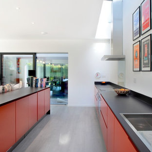 Inspiration for a large contemporary galley open plan kitchen in Hertfordshire with flat-panel cabinets, orange cabinets, blue splashback, glass sheet splashback, stainless steel appliances, a drop-in sink, quartzite benchtops, dark hardwood floors and with island.