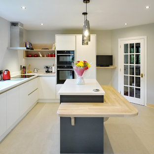 This is an example of a medium sized contemporary l-shaped kitchen in Other with flat-panel cabinets, white cabinets, an island and beige floors.