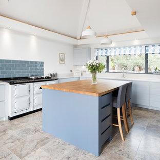 This is an example of an expansive contemporary u-shaped kitchen in Devon with flat-panel cabinets, blue cabinets, composite countertops, blue splashback, an island, white worktops, metro tiled splashback, white appliances and grey floors.
