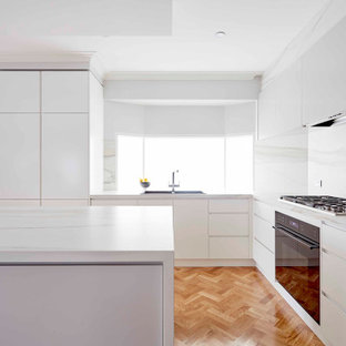 Modern l-shaped kitchen in Melbourne with a drop-in sink, flat-panel cabinets, white cabinets, white splashback, stone slab splashback, black appliances, medium hardwood floors, with island, brown floor and white benchtop.