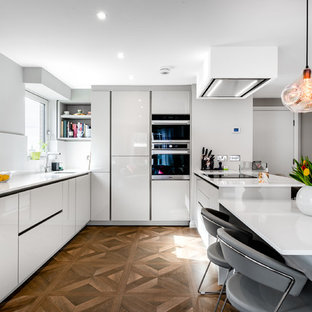Contemporary u-shaped kitchen in London with a submerged sink, flat-panel cabinets, white cabinets, stainless steel appliances, medium hardwood flooring, a breakfast bar, brown floors and white worktops.