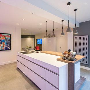 Inspiration pour une cuisine américaine design en U de taille moyenne avec un placard à porte plane, des portes de placard blanches, un électroménager noir et un îlot central.