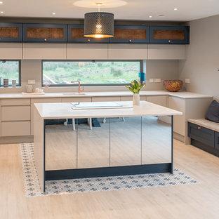 Immagine di una grande cucina contemporanea con ante grigie, isola, lavello sottopiano, ante lisce, paraspruzzi beige, elettrodomestici da incasso, parquet chiaro, pavimento nero e top beige