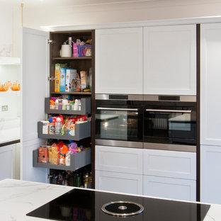 Modern inredning av ett stort kök, med en dubbel diskho, skåp i shakerstil, vita skåp, bänkskiva i kvartsit, spegel som stänkskydd, svarta vitvaror, mörkt trägolv, en köksö och brunt golv