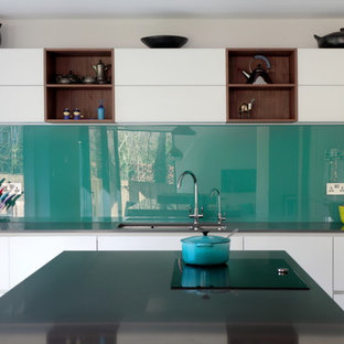 Design ideas for a large contemporary u-shaped open plan kitchen in Buckinghamshire with blue splashback, with island, a drop-in sink, flat-panel cabinets, white cabinets, quartzite benchtops, glass sheet splashback, stainless steel appliances and porcelain floors.