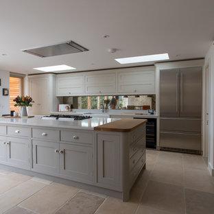 Exempel på ett mycket stort klassiskt gul gult kök, med en rustik diskho, skåp i shakerstil, grå skåp, bänkskiva i kvartsit, stänkskydd med metallisk yta, spegel som stänkskydd, rostfria vitvaror, kalkstensgolv, en köksö och beiget golv