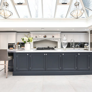 This is an example of a large traditional l-shaped kitchen/diner in Berkshire with granite worktops, an island, white worktops, white floors, recessed-panel cabinets, white cabinets, black splashback, glass sheet splashback and stainless steel appliances.