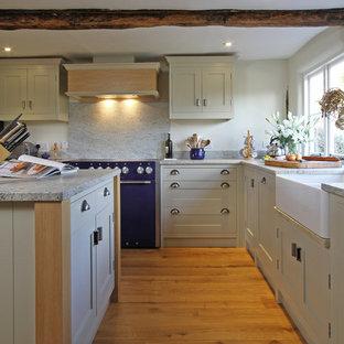 ハンプシャーのカントリー風おしゃれなL型キッチン (エプロンフロントシンク、御影石カウンター、シェーカースタイル扉のキャビネット、ベージュのキャビネット、カラー調理設備、白いキッチンパネル、石スラブのキッチンパネル) の写真