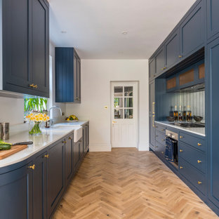 Inspiration for a large traditional galley kitchen/diner in London with a belfast sink, shaker cabinets, blue cabinets, composite countertops, mirror splashback, stainless steel appliances, no island and white worktops.