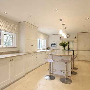 Photo of a large traditional kitchen in Hampshire with a farmhouse sink, shaker cabinets, white cabinets, granite benchtops, coloured appliances, limestone floors and with island.