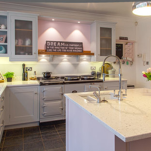 Eat-in kitchen - mid-sized farmhouse l-shaped slate floor eat-in kitchen idea in Hertfordshire with an undermount sink, shaker cabinets, gray cabinets, quartz countertops, gray backsplash, glass sheet backsplash and an island