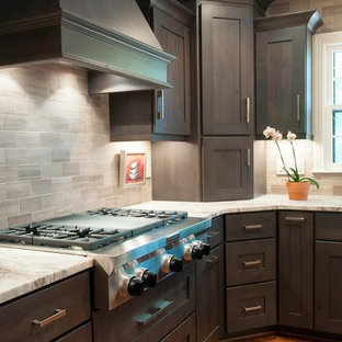 Mid-sized transitional eat-in kitchen remodeling - Inspiration for a mid-sized transitional l-shaped medium tone wood floor eat-in kitchen remodel in Nashville with an undermount sink, shaker cabinets, dark wood cabinets, granite countertops, gray backsplash, stone tile backsplash, stainless steel appliances and an island