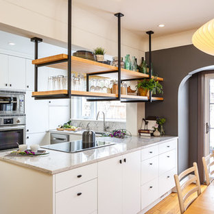 Photo of a small industrial u-shaped kitchen/diner in Ottawa with flat-panel cabinets, white cabinets, granite worktops, white splashback, stainless steel appliances, an island, a submerged sink, stone slab splashback, slate flooring and grey floors.