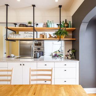Idéer för ett litet industriellt kök, med släta luckor, vita skåp, granitbänkskiva, vitt stänkskydd, rostfria vitvaror och en köksö
